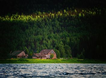 Beautiful landscape with lake and houses in the forest - image #136225 gratis