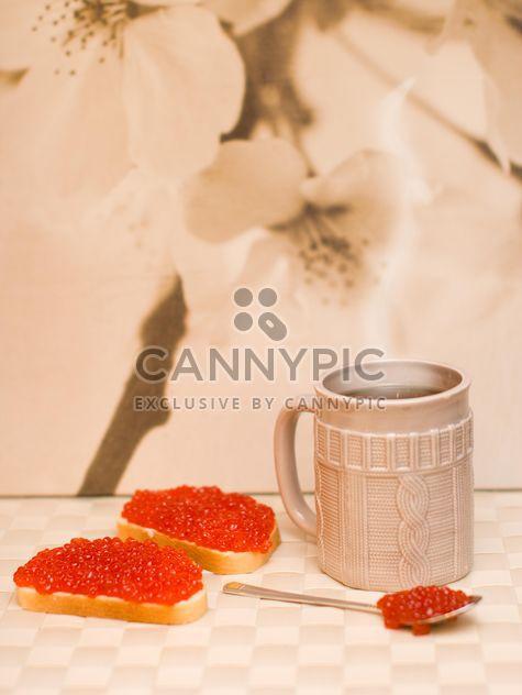 Sándwiches con caviar rojo y taza de té - image #182535 gratis