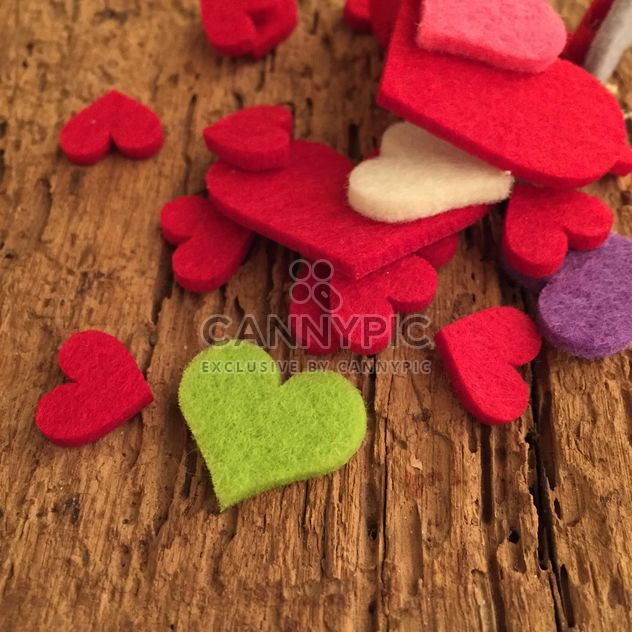Corazones de fieltro en la superficie de madera - image #182945 gratis