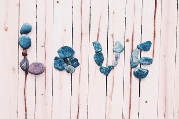 Word Love made of stones on wooden background - бесплатный image #184115