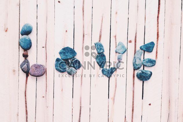 Amor palabra de piedras en el fondo de madera - image #184115 gratis
