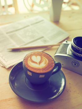 Latte, old camera and newspaper on the table - image gratuit #186945