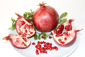 Ripe red pomegranate on white plate - бесплатный image #187825