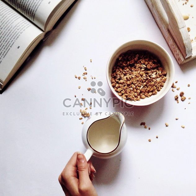 Oatmeal in a bowl, milk and book on white background - Free image #198375