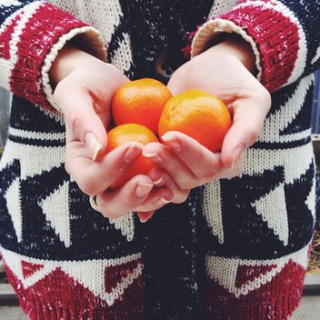 Tangerines in female hands - image #198395 gratis