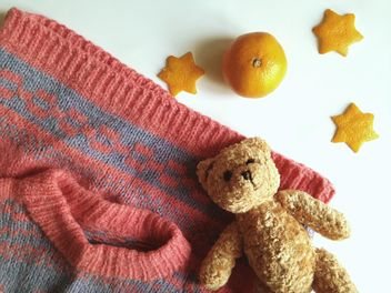 Children's sweater and a toy bear, tangerines on a white background - бесплатный image #198785