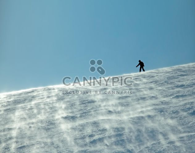 Silhouette of man on snowy hill - Free image #198865