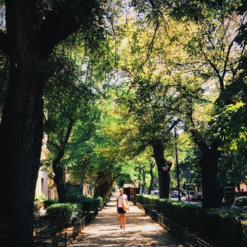 Girl walking in the street with green trees - image gratuit #271685