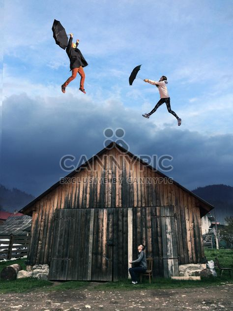 Boy looking at the girl and guy flying with umbrellas over the wooden house, #mylook - Free image #271695