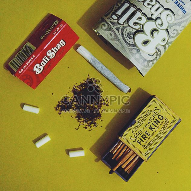 Rolled cigarette, tobacco, filter, cigarette paper and old matches over yellow background - Free image #272205
