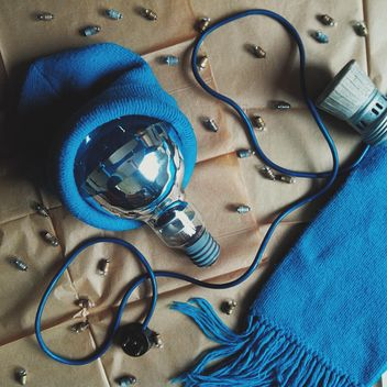 Light bulb in blue hat, scarf and tiny bulbs - image #272235 gratis