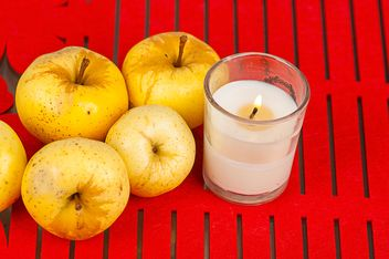 Yellow apples and candle on red background - Free image #272525