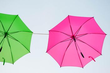 Green and pink umbrellas hanging - image #273065 gratis