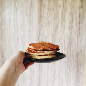 Pancakes on the plate in the hand - бесплатный image #273895