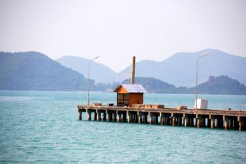 Wooden pier in the sea and mountains on the background - image #274805 gratis