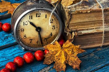 Old alarm clock, old books, beads and yellow autumn leaves on blue wooden background - бесплатный image #302085