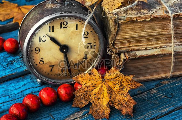 Old alarm clock, old books, beads and yellow autumn leaves on blue wooden background - Free image #302085