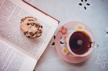 Tea with cookies and a book - image #302955 gratis