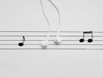 Earphones and notes on white background - image gratuit #304105