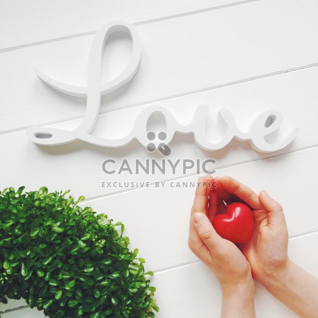 Heart in hands, word Love and green wreath on white background - Free image #329295