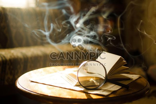 Burning incense sticks and open book through a magnifying glass - Free image #330405