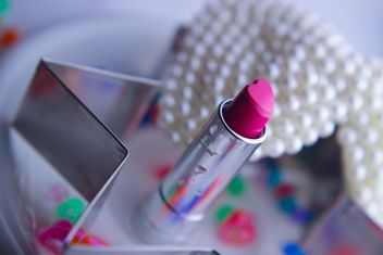 Pink makeup lipstick and pearls on a plate - бесплатный image #341485