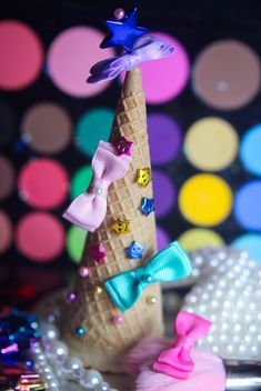 Icecream cone with ribbons and stars on a background of colorful eyeshadow palette - бесплатный image #341495