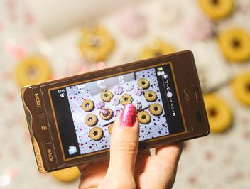 Smartphone decorated with tinsel in woman hands - бесплатный image #342175