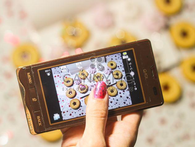 Smartphone, orné de guirlandes dans les mains de la femme - image gratuit #342175