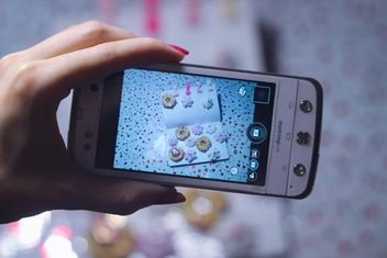 Smartphone decorated with tinsel in woman hands - image #342185 gratis