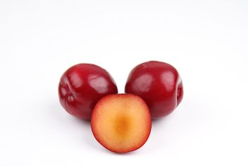 Red plums on white background - image gratuit #342465