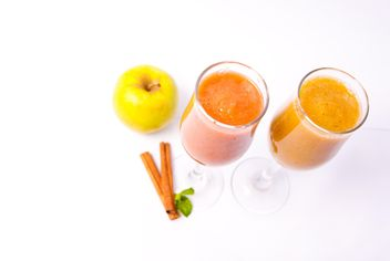 Citrus fresh juice in two glasses with cinnamon and apple - бесплатный image #342505