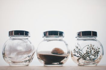 Small jars with decorations on white background - image gratuit #342545