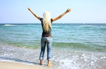 Young blond woman standing aback on sea shore - бесплатный image #344075