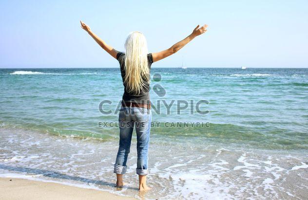 Joven mujer rubia pie desconcertado a orilla del mar - image #344075 gratis