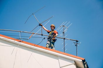 Worker installing antenna on roof top - бесплатный image #344535