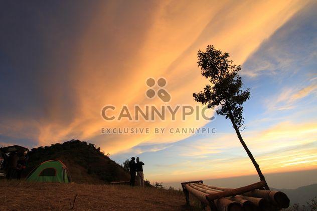 Touristes près de la tente sous un ciel nuageux au coucher du soleil - Free image #344605
