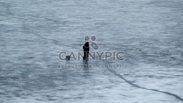 Pescador durante la pesca de invierno en río helado -  image #344625 gratis