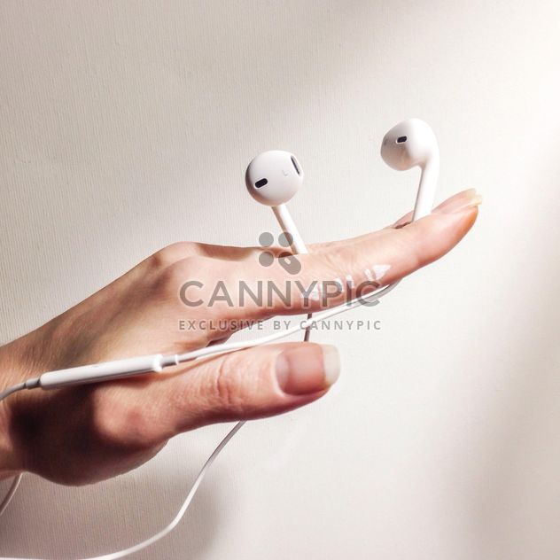 White earphones in female hand - бесплатный image #345055