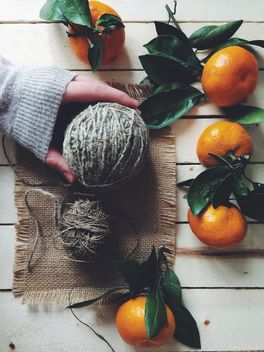 Skeins of wool and tangerines on white wooden background - бесплатный image #136255