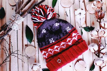 Wool hat and branches of cotton on wooden background - image #136265 gratis