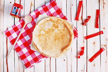 Pancakes, wooden spoon and checkered dishcloth on wooden background - Free image #136445