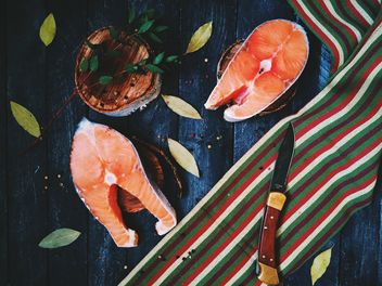 Salmon, bay leaves and knife on wooden background - бесплатный image #136475