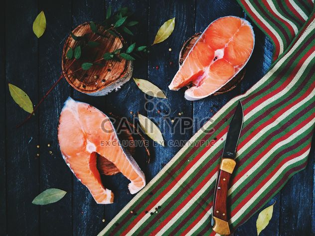 Salmon, bay leaves and knife on wooden background - Free image #136475
