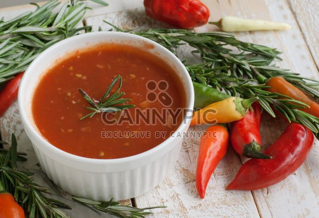 tomato sauce with rosemary and chili peppers on a wooden table - image #183365 gratis
