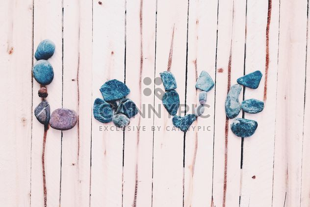 Word Love made of stones on wooden background - image gratuit #184115