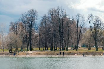 People on shore of lake in spring - image #186065 gratis