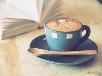 Coffee latte art and open book on wooden table - image #187075 gratis
