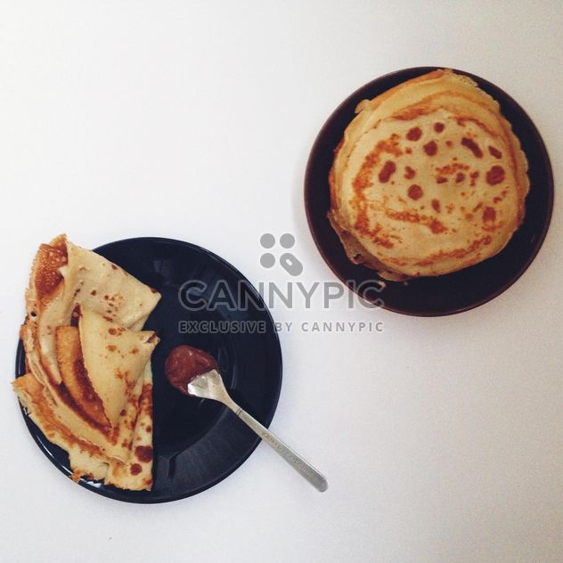 Tasty pancakes on black plates - image #198495 gratis