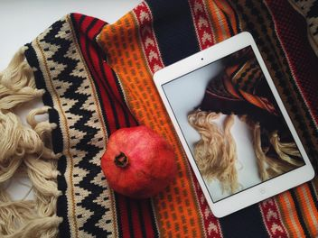 warm scarf and fresh pomegranate on white background - image gratuit #198765